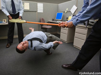A businessmen and two co-workers playing limbo with broom in office-cubicle environment. The men are wearing dress shirts and ties. Two of the businessmen are holding the ends of the broom and the third is limbo dancing under it.